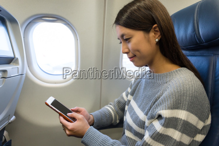 woman using mobile phone in plane