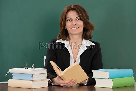 female teacher sitting at classroom desk
