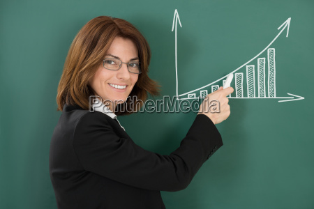 young happy female teacher holding chalk