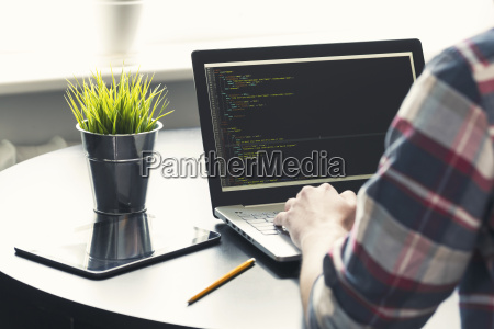 programmer working on laptop at office