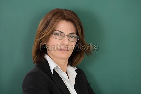 female teacher standing against green chalkboard