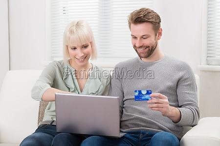 couple shopping online using laptop