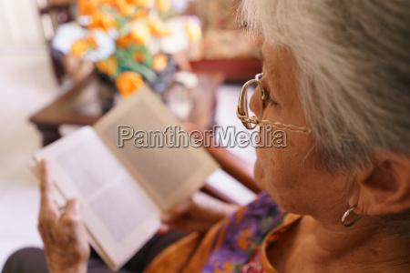 old lady lettura libro su poltrona