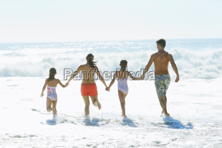 family running into surf at beach