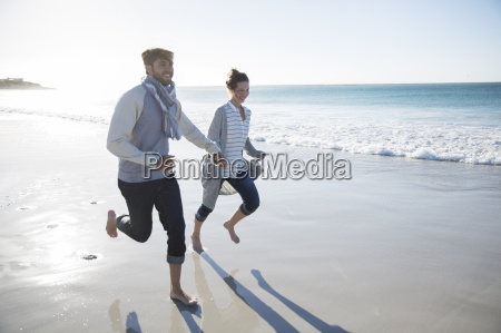 young couple holding hands and running