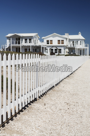 white picket fence leading to beach