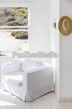 armchair next to window overlooking beach