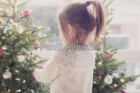 ragazza che decorano albero di natale
