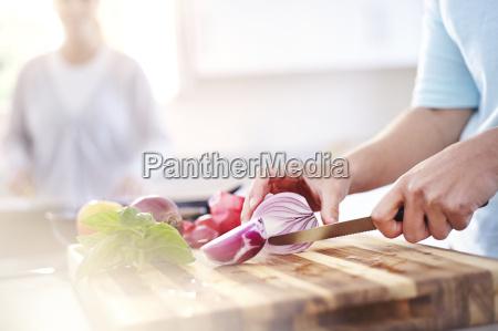 donna tagliando cipolla rossa sul tagliere