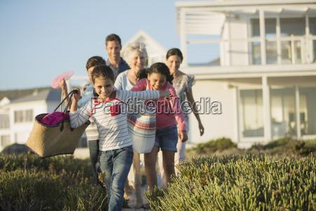 family walking on beach path outside