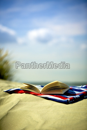 open book on towel at sandy