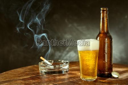 sigaretta accesa e birra fredda in