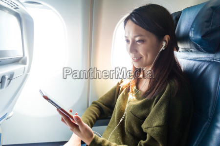 woman passenger in airplane using cellphone