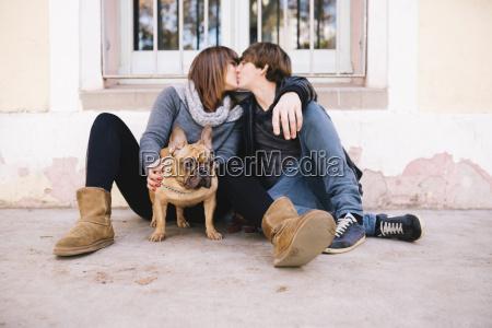 giovane coppia con bulldog francese seduto