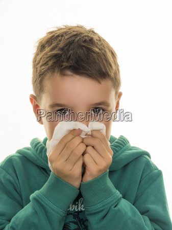 portrait of boy blowing his nose