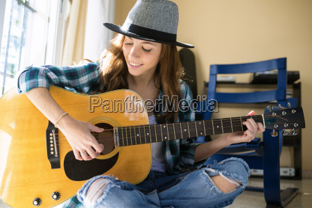 smiling young woman playing guitar indoors