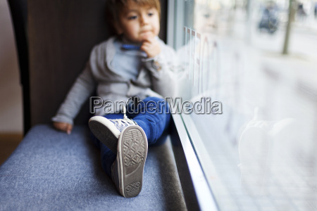 little boy sitting on window sill