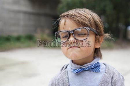 portrait of little boy wearing oversized