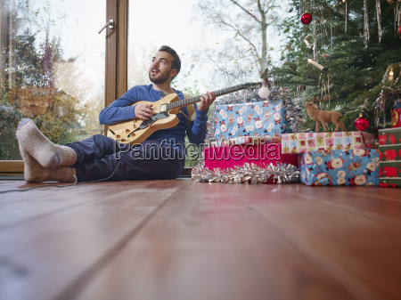 man sitting on floor and playing