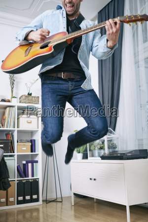 enthusiastic young man at home playing