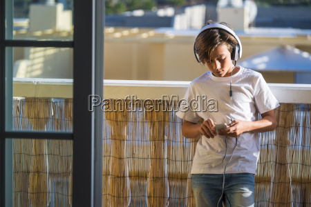 boy listening music with headphones and