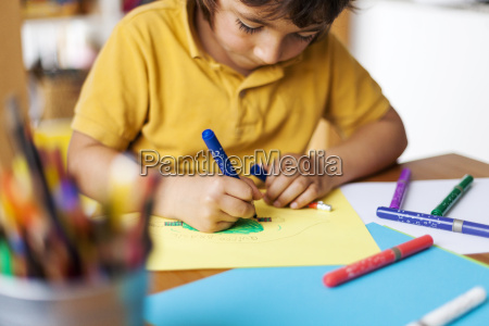 little boy drawing on yellow paper