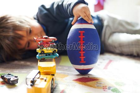 boy lying on floor with football