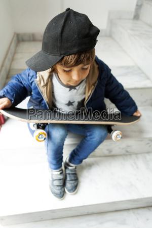 boy sitting on stairs holding skateboard