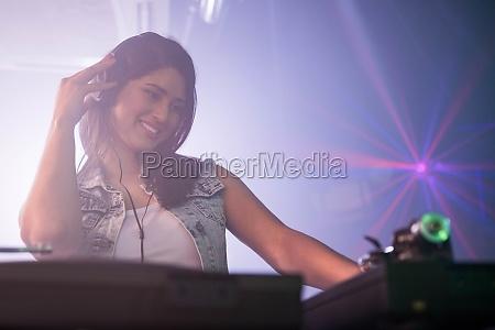 pretty female dj playing music