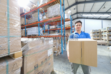 worker lifting box and smiling at