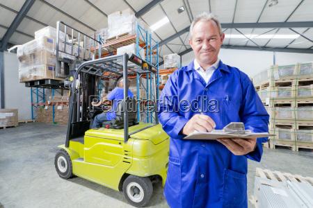 warehouse supervisor worker smiling at camera