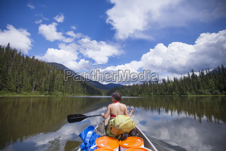a woman paddles a canoe over
