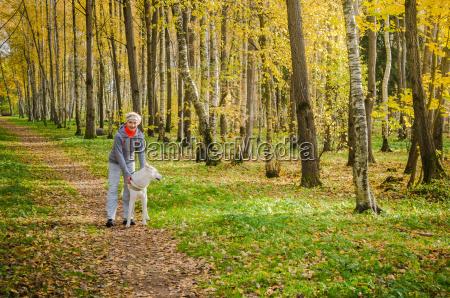 donna con cane che cammina nel