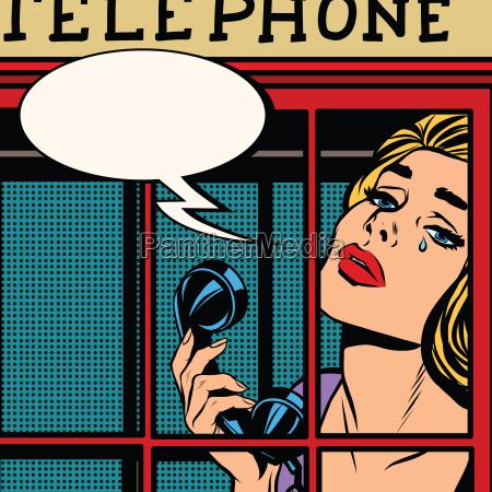 ragazza che piange nella cabina telefonica
