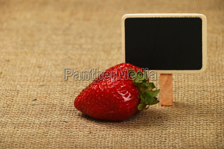 one big strawberry with price sign