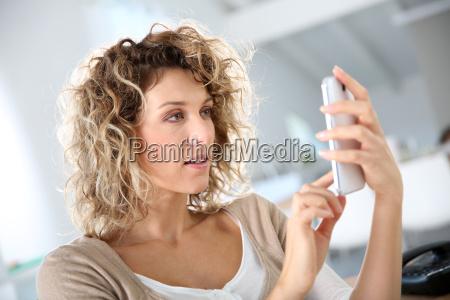 donna in ufficio invio messaggio con