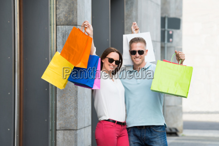 couple holding multi colored shopping bag