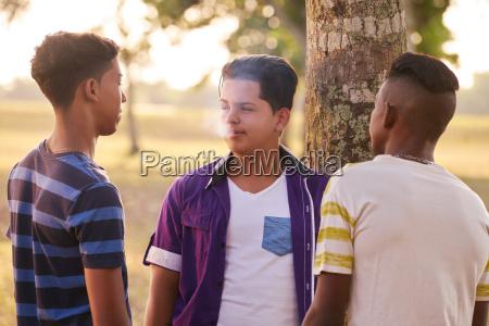 adolescenti nel parco ragazzo fumare sigaretta