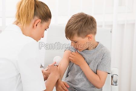 medico dando uniniezione al ragazzo
