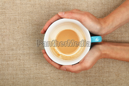 two woman hands holding cappuccino coffee