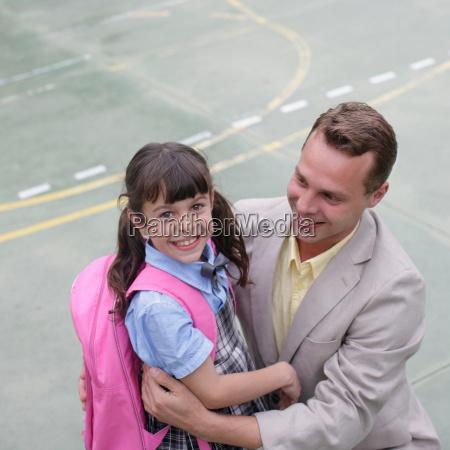school girl hugging father