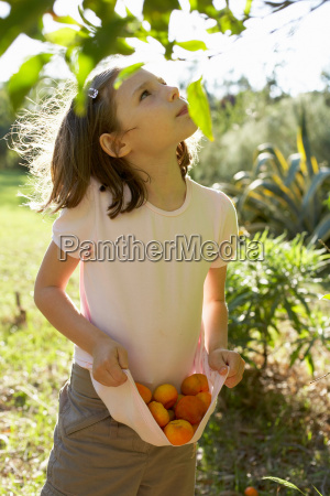 young girl outside collecting fruit