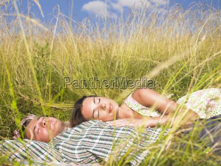 coppia disteso campo erba alto