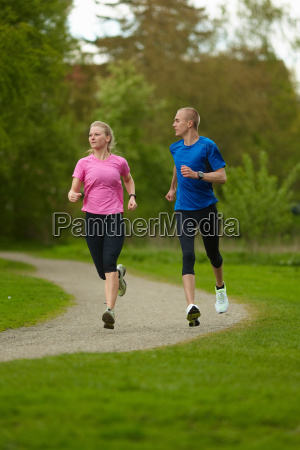 man and woman running in nature