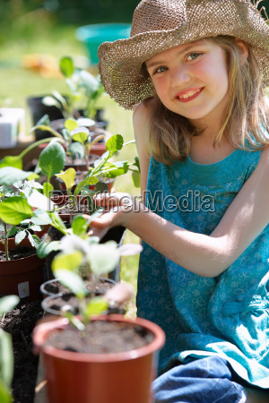 young girl looking at vegetable plants