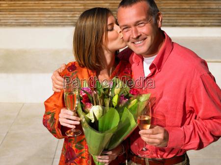 woman kissing mature man on cheek