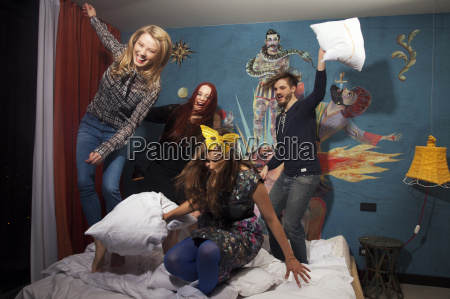 four adult friends having pillow fight