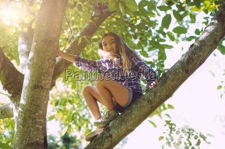 girl sitting on branch of tree
