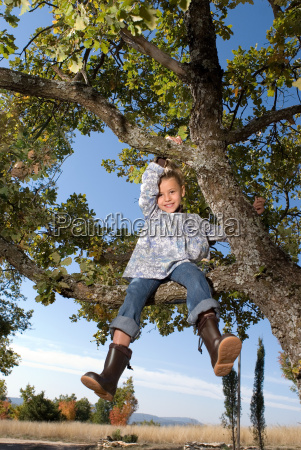 young girl climbing in a tree