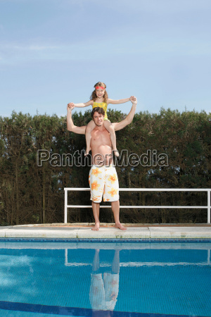 father carrying girl by pool